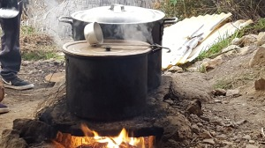 Two big pots cook over an open fire. A ladle sits on one of the pots, which is steaming.