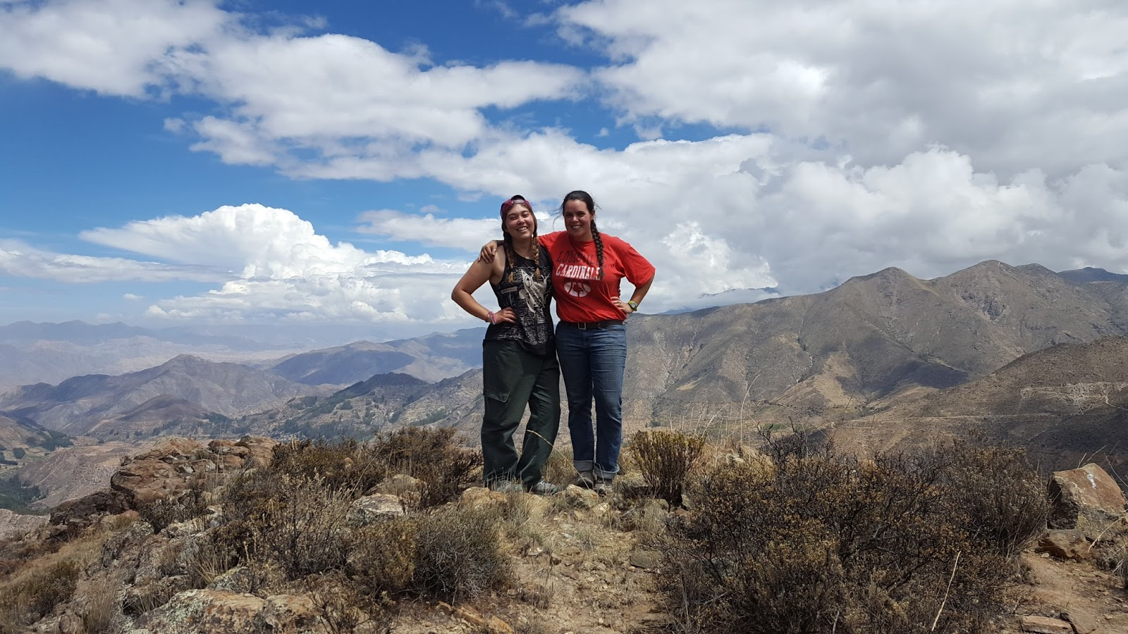 Faith and I stand together for a photo at the peak of a mountain, with a view of a mountain range behind us.