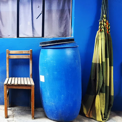 A blue 55 gallon water barrel sits out on the back patio between a checkered, green hammock and an old, worn wooden chair.