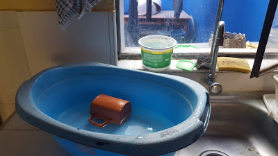 A small blue tub with water in it sits next to the indoor sink, an old plastic mug floating on the water's surface.