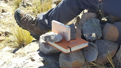 An iphone sits, propped between two rocks and on tops of a journal. The photographer's leg is visible behind it.