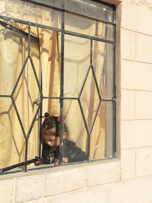 A four year-old neighbor looks down at her phone while leaning out the window of her house, her head squeezed between the bars.