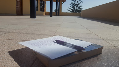 A pen and the beginnings of a letter sit on top of a book, out on the patio.