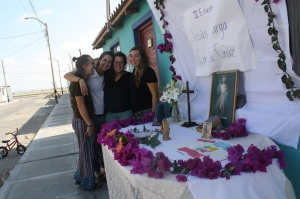Hannah, Kristin, Faith and I pose next to a table outside of our house, decorated to represent one of the stations of the cross. Different religious objects sit on the table such as bougainvillea flowers, a cross, praying hands and a photo of Jesus.