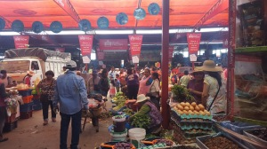 A photo of the market place. Vendors sell different produce and buyers move about through the stalls and between trucks.