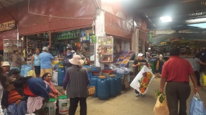 A corner in the marketplace. A store featuring many blue barrels filled with different produce. Vendors sit and stand about and talk to customers.
