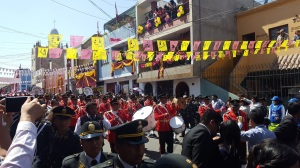 A band marches in the parade, banners of papel picado waving above their heads, tied from house to house as they stretch across the street.