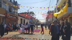 A street in the middle of Tacna during the anniversary. People mill about and pose for photos next to the artwork made out of colored sawdust on the road.