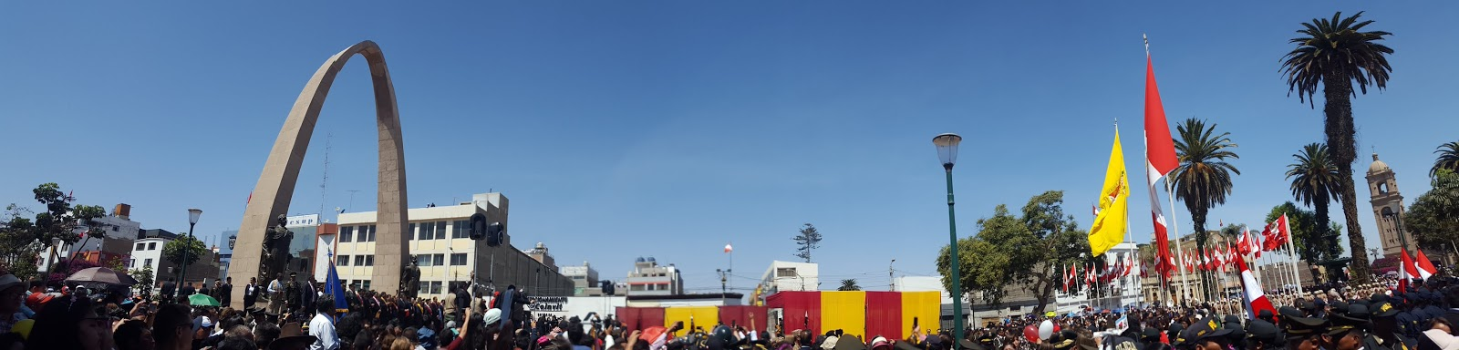 A panorama photo of the main plaza during the anniversary of the city. A huge crowd gathers amidst the famous Tacna arch and many Peruvian flags waving in the wind.
