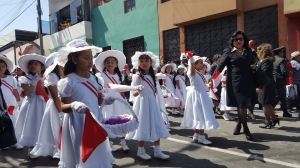 Small girls in white dresses and hats carry baskets of bougainvillea flowers as they march in the parade.