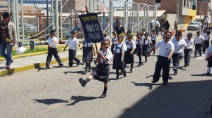 A student carrying a banner for her class, marches in unison with the others.