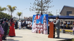 A teacher from a nearby school speaks into a microphone as he stands at a podium in the plaza next to the school. Students in costume re-enact a scene from the Peruvian Chilean conflict with a backdrop of the cathedral as their scenery.