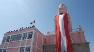 A photo of one of the churches in the center of the city shows a long Peruvian flag hanging from the bell tower. Spectators watch from the roof.