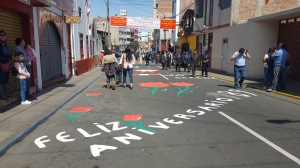 A photo of spectators walking down the street. Sawdust decorations read Feliz aniversario and red roses with green stems.