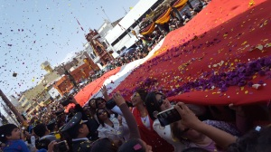 A photo of the parade. The largest Peruvian flag is carried by the women of Tacna. Yellow and purple confetti rain down from the sky.