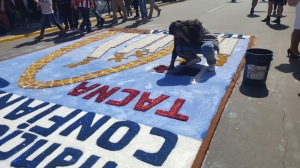 An artist touches up her sawdust artwork that depicts heroic figures and the famous arch of Tacna.
