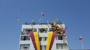 Atop a tall building, spectators dump many yellow and burgundy balloons onto the crowds below.