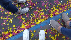 A photo of three pairs of feet. Yellow and burgundy confetti litters the ground.