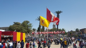 A photo of the main plaza. Groups of spectators mill about. A large Peruvian flag and a Tacna flag blow in the wind.