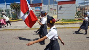 """The """"escolta"""" or class representatives march in unison together. The student in the center carries a Peruvian flag."""