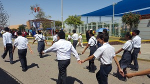 Students from Colegio Miguel Pro march in unison down a street in Habitat.