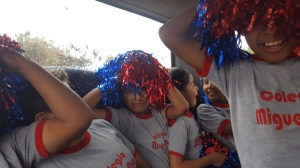 Students with red and blue pom poms goof around on the bus.