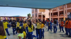 A team of students dance in a circle in the school's patio while others look on.