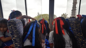 Students with red and blue ribbons in their hair look out the window of the bus.