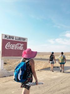 """Walking down a dirt road, returning from the beach. There is a sign that reads """"Play Llostay"""" or """"Llostay Beach"""" with an advertisement for coca-cola beneath it. I am in the foreground walking away, carrying a beach umbrella and a backpack and wearing a large straw hat."""