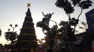 The giant Christmas tree in downtown Tacna, in the foreground there is a statue of Santa and a reindeer that leaps up into the sky.