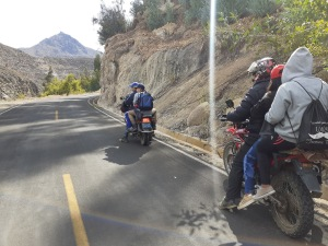 Students ride on the back of motorcycles, two to three riders on the back of each bike.