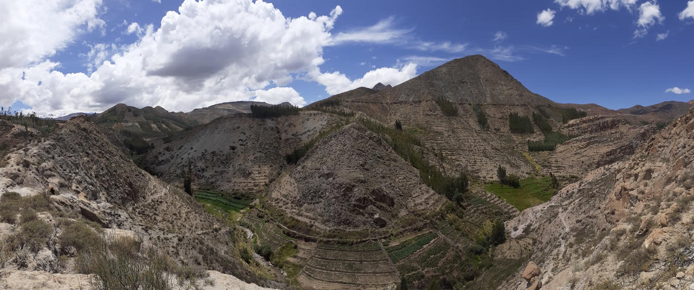 A panorama photo of the mountains taken on a ridge next to Estique Pueblo. Below are terraces of different farms.