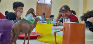 Students seated around a table, waiting for lunch. In the foreground are mugs, plates and a plastic toy camel.