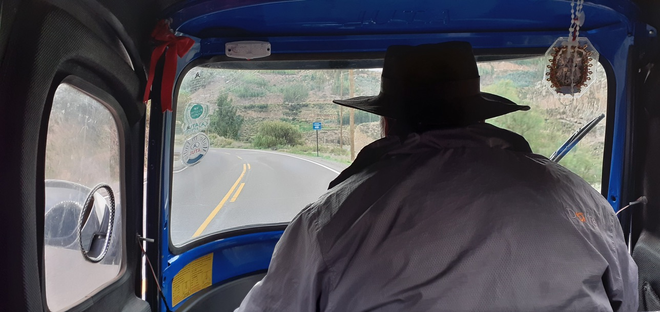 A photo taken from the back seat of the three-wheeled moto-taxi. The driver's back can be seen. He wears a jacket and a wide brim hat.
