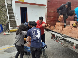 Students and a profesor unload bricks from the back of a truck into a wheelbarrow.