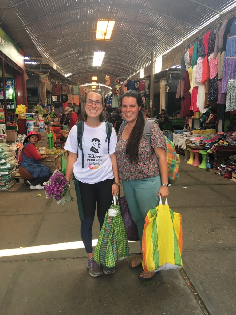 Hannah and Faith stand in the clothing section of Mercado Grau. They are smiling, carrying backpacks and holding market bags full of groceries.