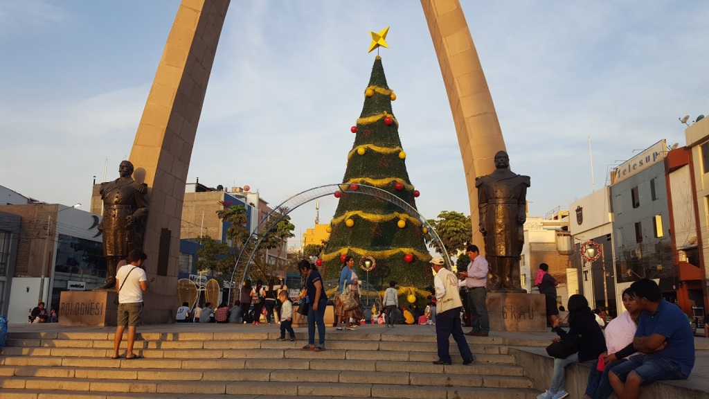 A photo of the giant christmas tree in downtown Tanca, with the arch of Tacna in the foreground. People mill about and visit with each other.