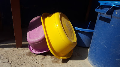 Two tubs, known as baldes, used for washing clothes are overturned and stored under a table.