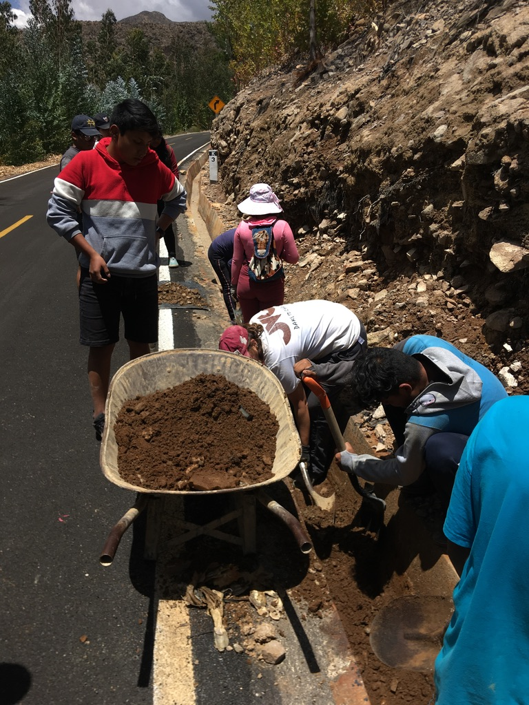 Students and I cleaning out another ditch. A wheel barrow sits next to the ditch, half-filled with dirt and debris. A student looks down at us while we work while he waits by the wheelbarrow.