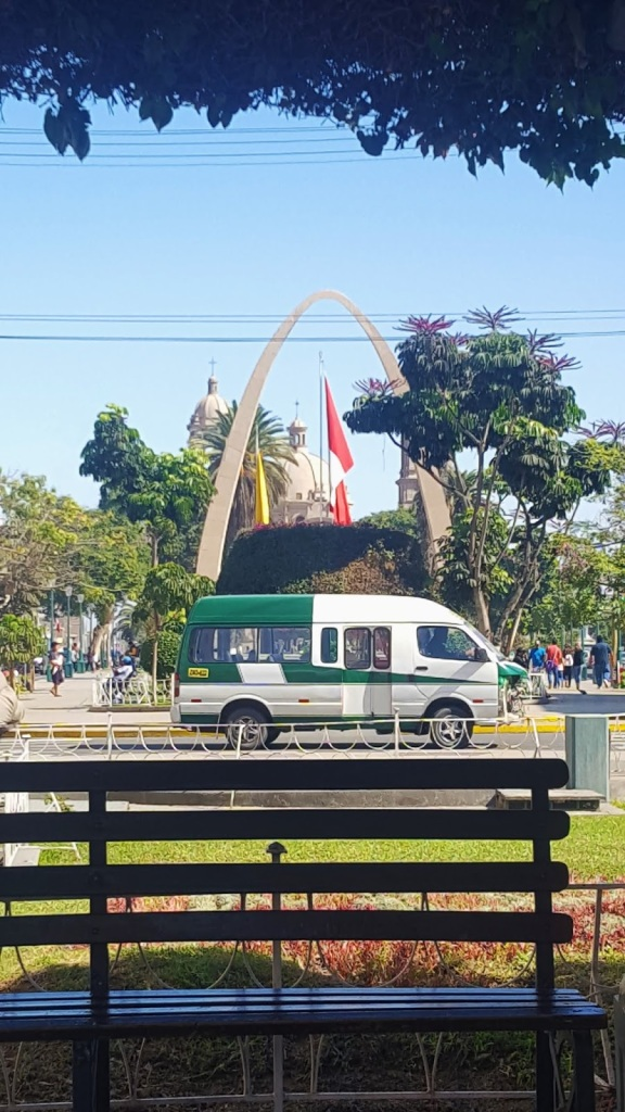 "A mini-bus known as a ""combi"" drives down one of the main streets of Tacna, with the famous arch in the background."