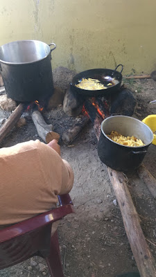 A photo of the cooking fires. A pot and a pan sit on top of smoldering fires, with an extra pot filled with cooked french fries to the side.