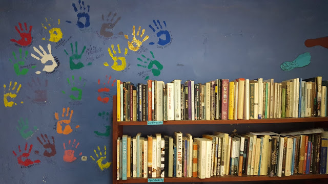 One of the bookshelves in the Jesuit Volunteer house in Tacna. Handprints from past volunteers are painted in different colors on the wall behind it.