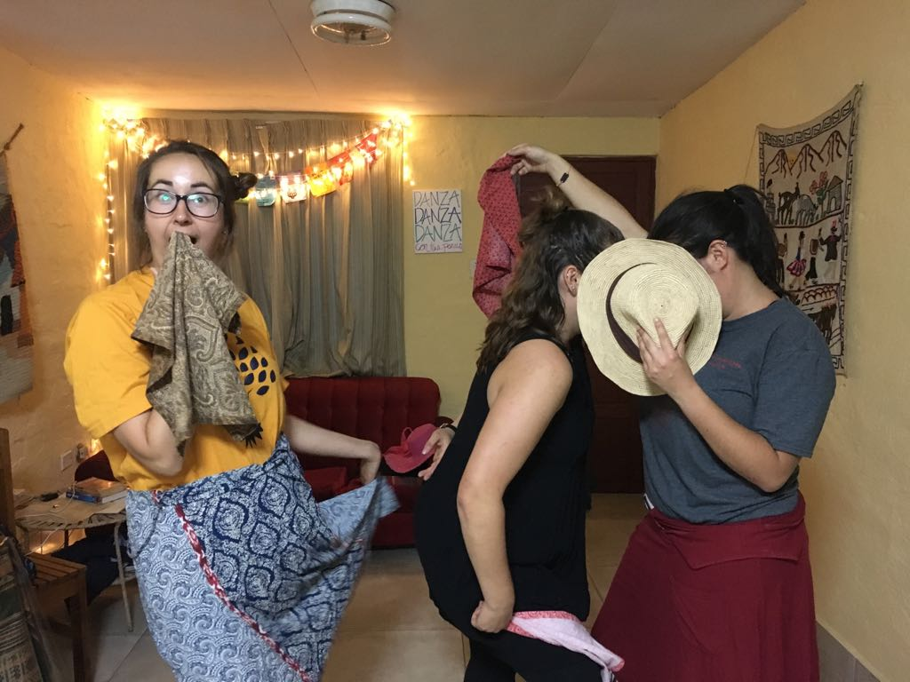 Kristin, Faith and I pose during a community night where we learn a dance called the marinera. Kristin stands with a handkerchief and a hand to her mouth. Faith and I hide together behind a straw hat, pretending to kiss.