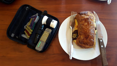 A photo of a bloodtesting kit, showing a high blood sugar reading, next to a chocolate croissant on a plate with knife and fork.