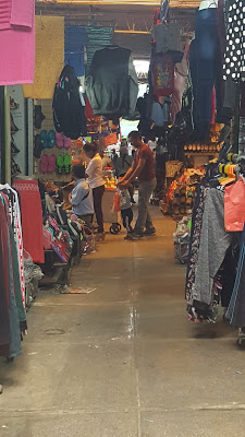 A photo of the clothing section in Mercado Grau with clothing hanging from racks and the ceiling.