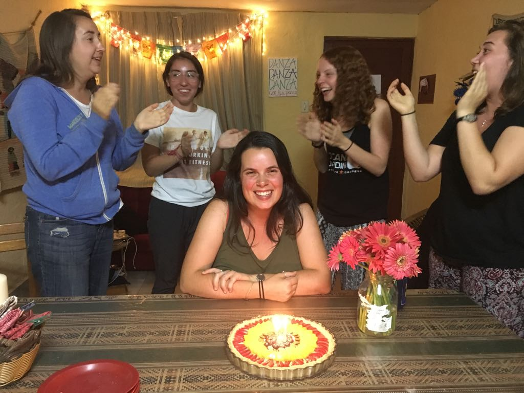 Three generations of Jesuit volunteers stand around Faith and sing her happy birthday as she sits at the kitchen table. There is a fruit tart with a lit candle in front of her.