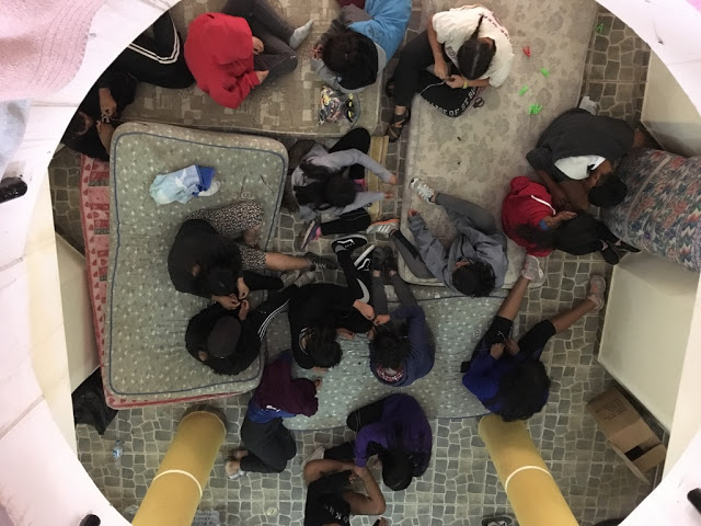 A view from the second floor down to the first where students rest on mattresses and make friendship bracelets.