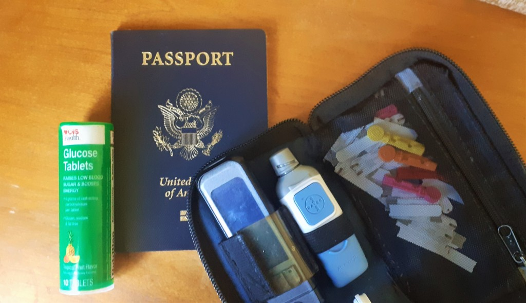 A photo of a vial of glucose tablets, a passport and a kit used to test blood glucose levels.